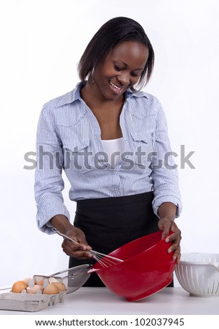 Young South African woman whisking egg in a red bowl. - stock photo