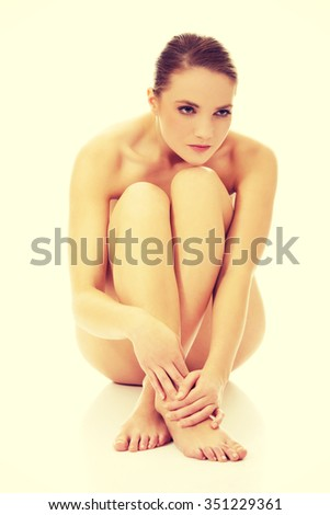 Young spa woman sitting on the floor with her knees close to chest.