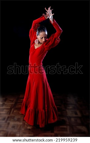 young Spanish woman flamenco dancer dancing Sevillanas show wearing traditional folk red dress in traditional Dance of Spain concept performing show on wooden stage