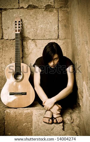 Young spooky guitarist staring at camera. - stock photo