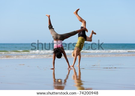 Young sport couple - Caucasian man and African-American woman � doing gymnastics on the beach - stock photo