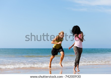 Young sport couple - Caucasian man and African-American woman - jogging on the beach in a playful mode