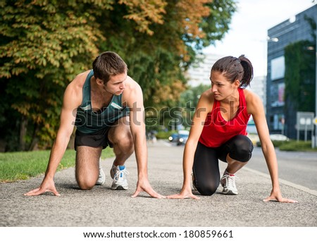 Young sport couple in starting postion prepared to compete, looking on each other - stock photo