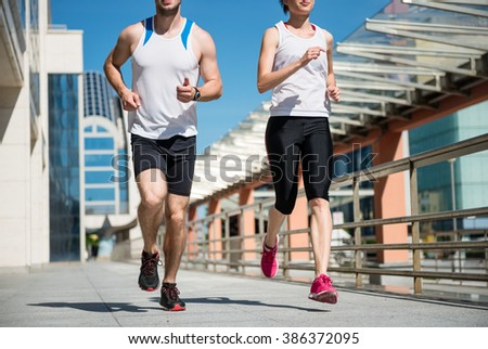 Young sport couple jogging together in city environment - crop - stock photo