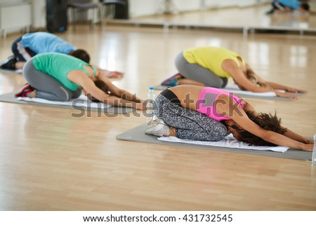 Young sport group doing yoga exercises in fitness class - stock photo