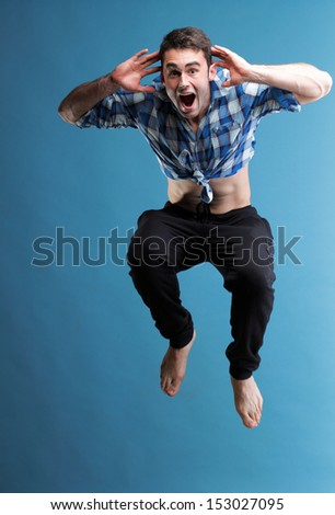 Young sport man jumping over blue background - stock photo