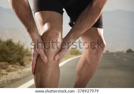 young sport man with strong athletic legs holding knee with his hands in pain after suffering muscle injury during a running workout training in asphalt road in muscular or ligament wound  - stock photo