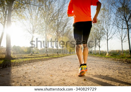 young sport man with strong calves muscle running outdoors in off road trail ground with trees under beautiful Autumn sunlight in fitness, countryside training and healthy lifestyle concept