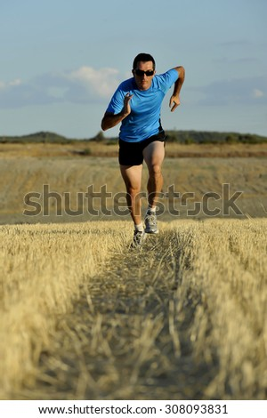 young sport man with sunglasses running outdoors on straw field ground in frontal perspective towards camera in healthy lifestyle and summer training concept - stock photo