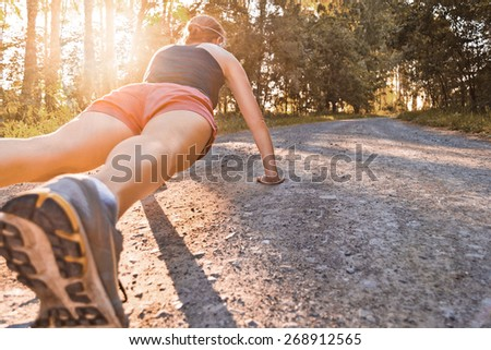 Young sport woman does pushups on the summer forest road
