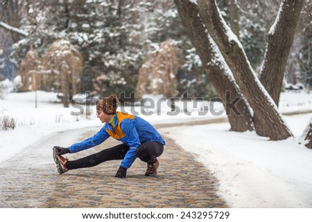 Young sport woman doing exercises during winter training outside in cold snow weather - stock photo