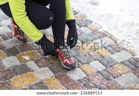 Young sport woman model tying running shoes during winter training outside in cold snow weather in park  - stock photo