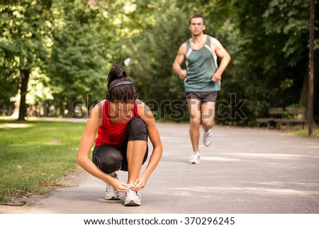 Young sport woman tying shoelace, man in behind is jogging