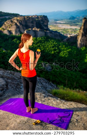 Young sport woman with drink bottle standing on the mat in the mountains.  - stock photo