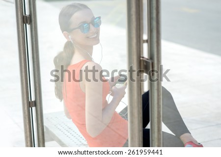 Young sport woman with phone waiting at the bus station. View through the glass reflection - stock photo