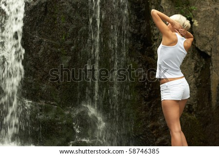 Young sporting girl in shorts at the outdoor near to waterfall - stock photo