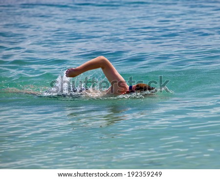 young sporting man swims in the sea - stock photo