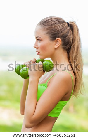 Young sporting woman with dumbells