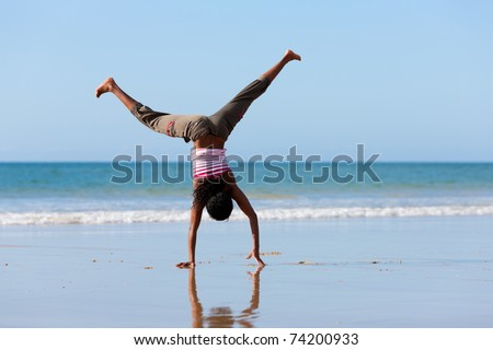 Young sportive African-American woman doing gymnastics on the beach - stock photo