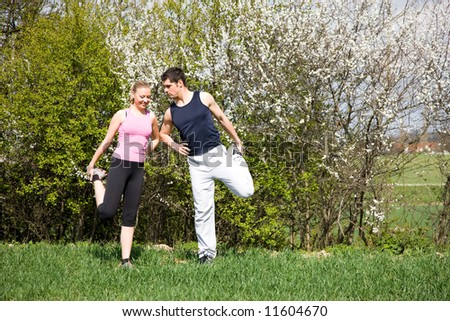Young sportive couple doing stretching exercises in a spring setting