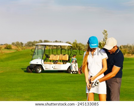 Young sportive couple playing golf on a golf course  - stock photo