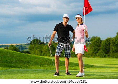 Young sportive couple playing golf on a golf course, they certainly do exercise or have training - stock photo