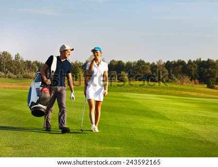 Young sportive couple playing golf on a golf course walking to the next hole - stock photo