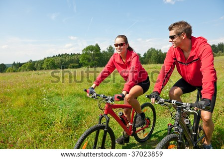 Young sportive couple riding mountain bike in spring meadow on a sunny day - stock photo