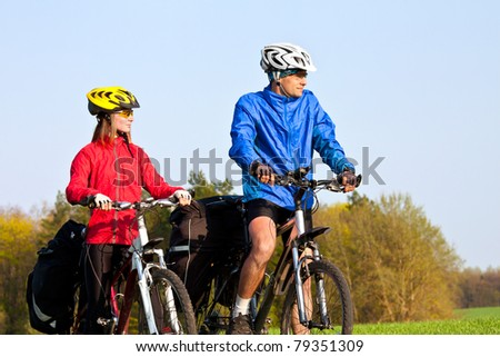 Young sportive couple with mountain bikes looking in one side