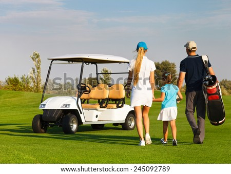 Young sportive family playing golf on a golf course - stock photo