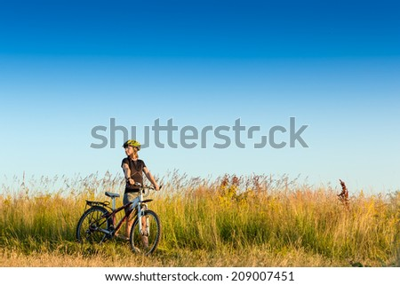 young sportive female biker in the summer meadow