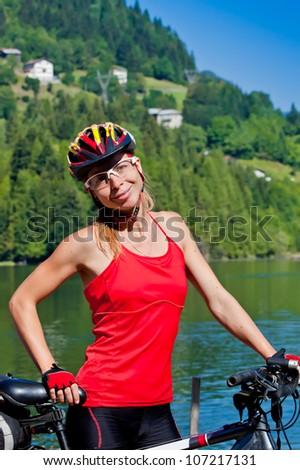 young sportive female biker outdoors on mountain bike - stock photo