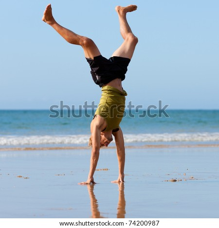 Young sportive man doing gymnastics on the beach - stock photo