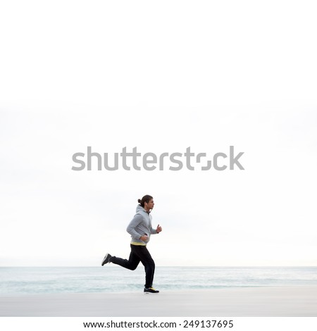 Young sportive man running along the beach listening to music on smart phone, athletic runner training on morning jog outdoors - stock photo