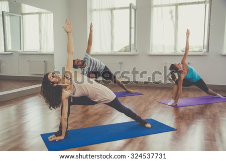 Young sportive trio group boy and two girls are practicing stretching exercises in the studio - stock photo