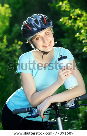 Young sportive woman  in the park with her bike - stock photo
