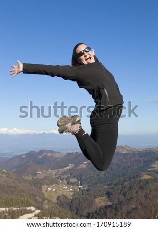 Young sportive women joyfully jumping in the mountains, with blue sky in background  - stock photo