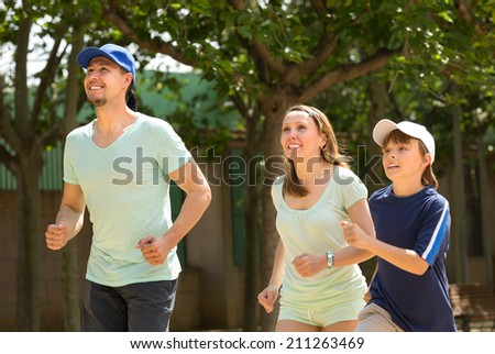 Young sports family doing running outdoor summer day - stock photo