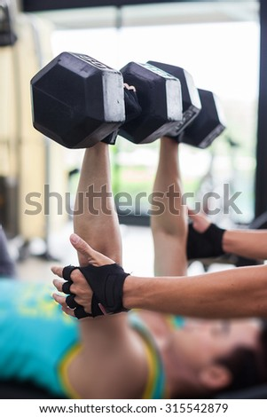 Young sports man doing exercises with dumbbells in the gym. Fitness.