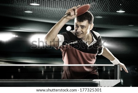 young sports man tennis-player in play on black background with lights - stock photo