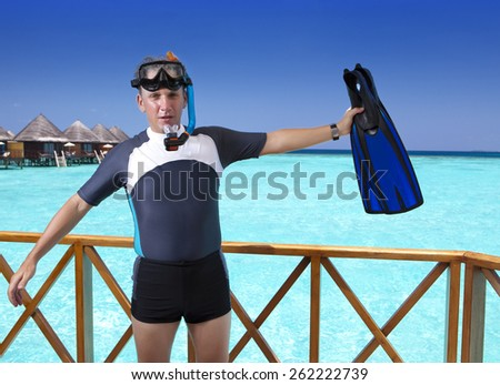 Young sports man with flippers, mask and tube on sundeck of a house over the sea. Maldives  - stock photo