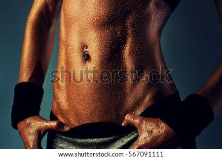 Young sports woman abdominal muscles. Sexy wet body close-up.