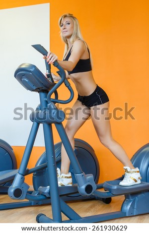 Young sports woman doing exercises on an elliptical trainer in the gym. - stock photo