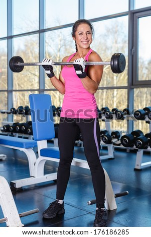 Young sports woman doing exercises with barbell in the gym. Fitness.