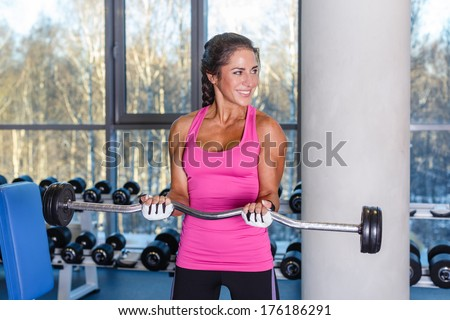 Young sports woman doing exercises with barbell in the gym. Fitness. - stock photo