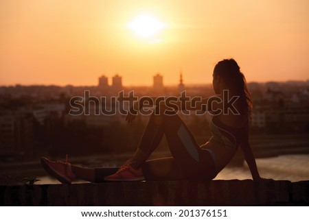 young Sports woman enjoying in the sunset after a hard workout - stock photo