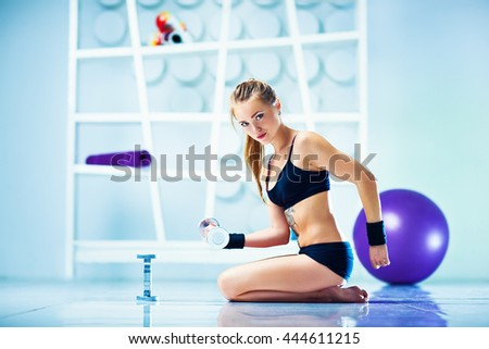 Young sports woman in black clothing with equipment in modern white interior. Tattoo on body. - stock photo