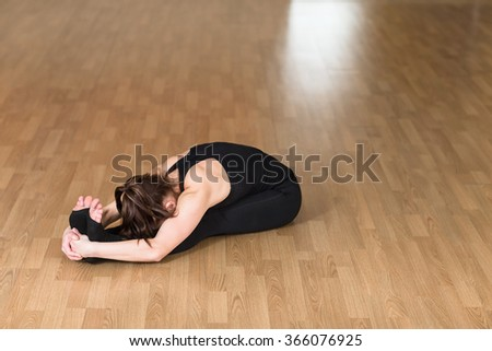 Young sports woman practicing yoga Pose. Indoor gym. - stock photo