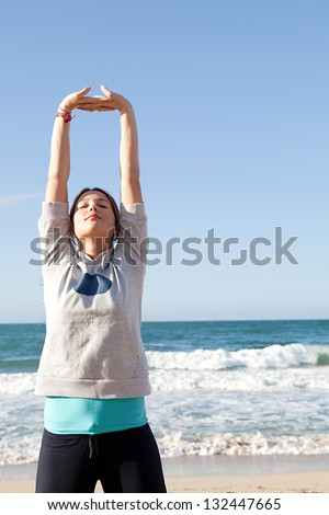 Young sports woman stretching her arms up with interlinked fingers while exercising on a beach with a blue sky and the sea in the background.