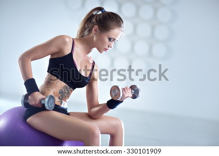 Young sports woman training with dumbbells sitting on fitness ball in white interior. Tattoo on body. - stock photo